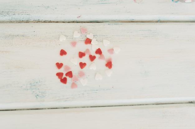 Сахарные сердечки лежат на деревянном.