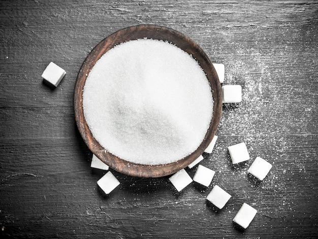 Сахар в деревянной миске. на черной доске.