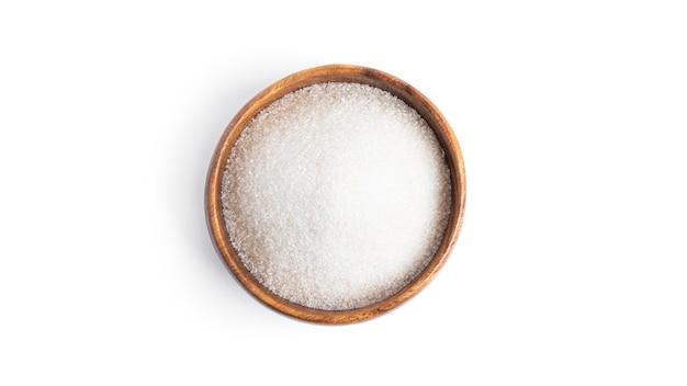 白い背景で隔離の木製プレートの砂糖。高品質の写真