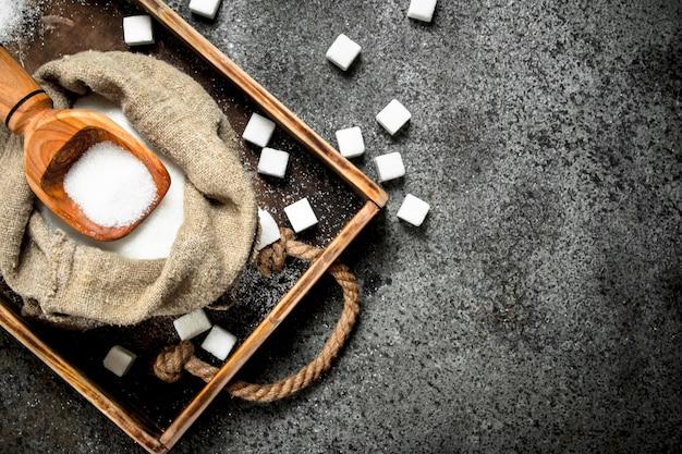Сахар в старом мешке с совком на деревенском фоне