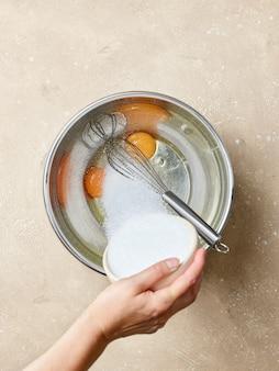 Сахар добавлен к яйцам в металлической миске на бежевом кухонном столе, вид сверху
