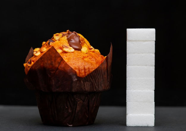 Sugar level next to the cupcake, cubes sugar stacked on top of each other, the amount of sugar in the dish