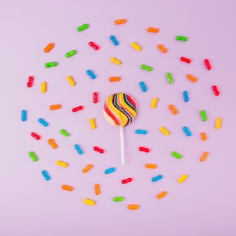 Sugar lollipop surrounded with colorful marmalade candies over pink background