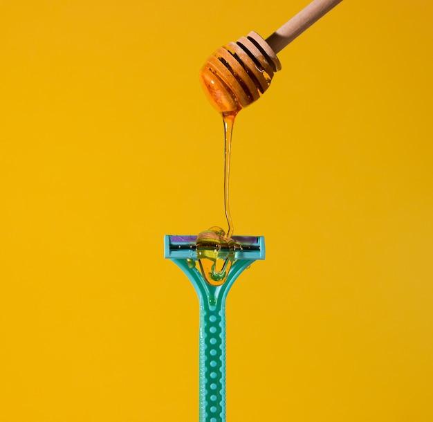 면도기에 대한 제모용 설탕 페이스트. 면도날에 슈가링 페이스트가 떨어집니다. 제모, 스파, 바디 케어의 개념.