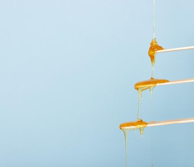 Sugar paste for hair removal runs down a wooden spatula