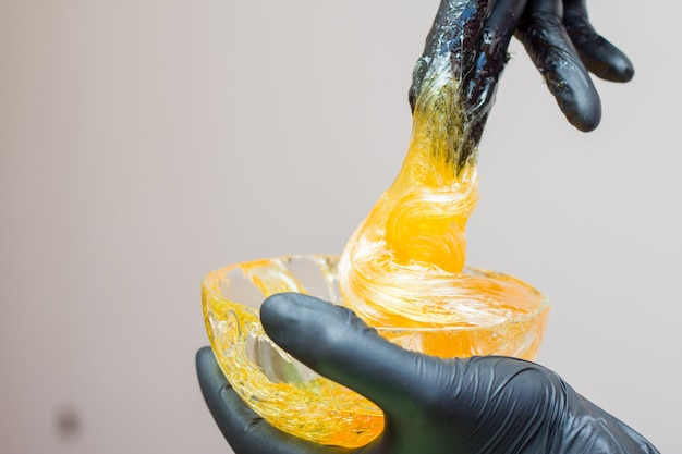 Sugar paste or wax honey for hair removing with black gloves hands of cosmetologist in spa salon