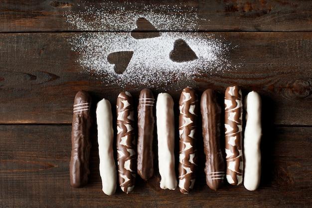 나무 책상에 설탕 가루 하트와 초콜릿 비스킷