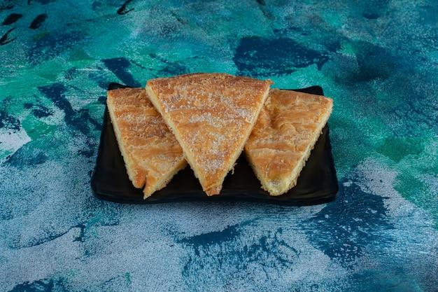 Сахарная пудра над хлебом на деревянной тарелке, на мраморном столе.