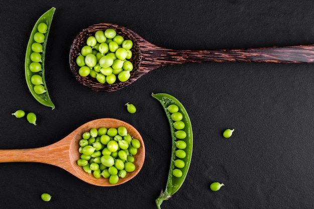 Sugar snap peas with mint on a rustic wood spoon
