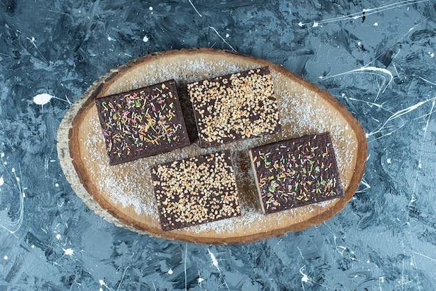 파란색 테이블에 있는 판자 위에 있는 초콜릿 와플에 설탕을 뿌립니다.