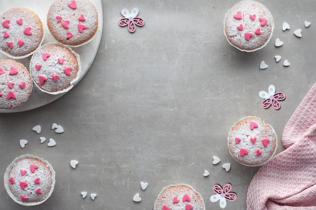 Sugar-sprinkled muffins with pink and white fondant icing hearts