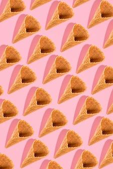 복사 공간이 있는 분홍색 배경 이미지에 패턴으로 배열된 아이스크림용 설탕 와플 콘은...