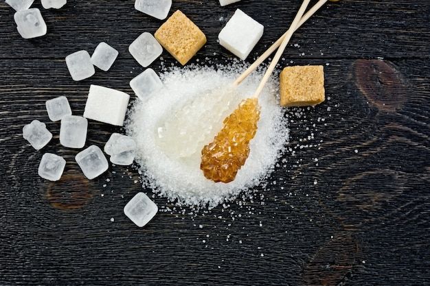 上から黒い木の板の背景に砂糖白と茶色の粒状、結晶と立方体