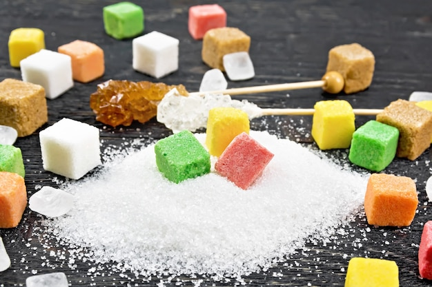 Sugar of white, brown, pink, green, yellow and different shapes on a wooden board background