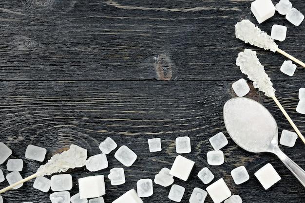 スプーンの砂糖の白い顆粒、黒い木の板の背景にフレームの形で棒の上の立方体と結晶