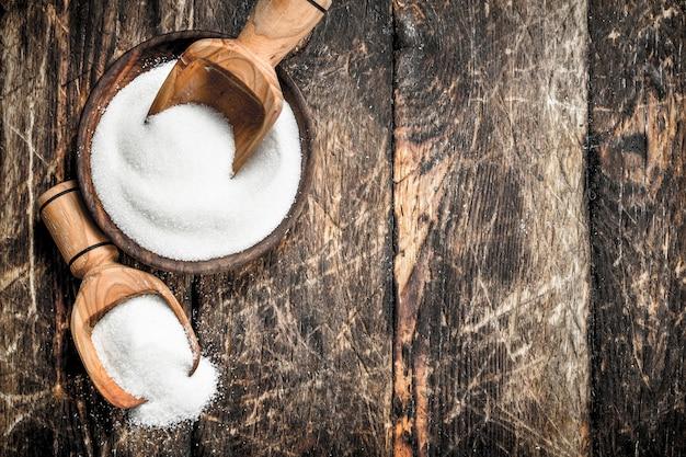 ボウルにスクープを入れた砂糖。木製の背景に。