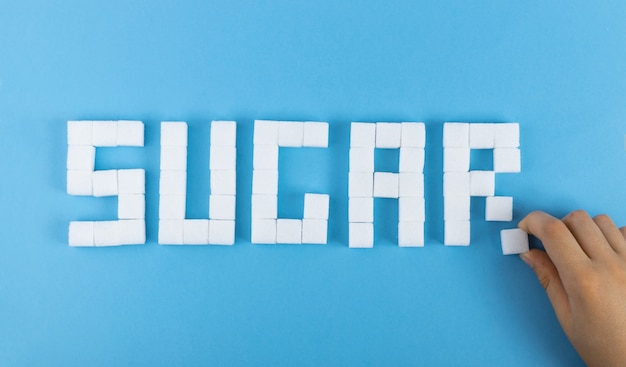 Слово сахара из кубиков белого сахара на синей поверхности. вид сверху нерафинированного тростникового сахара
