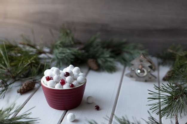 Sugared cranberries in red bowl with spruce branches and christmas decoration. traditional russian new year sweets.