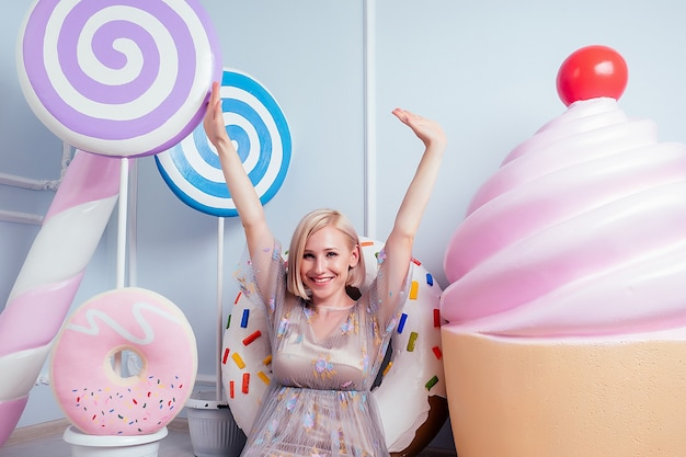 Sugaring concept. beautiful young blonde barbie sweet woman confectioner model perfect makeup sitting next to lollipop and fake confectionery sweets donut candy huge donuts cake background in studio