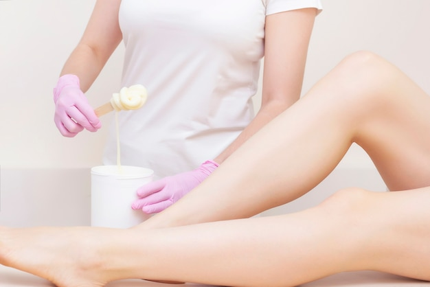 Sugaring. depilation with sugar. woman having legs hair removal procedures in a salon. depilation concept