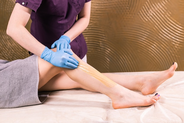Sugaring epilation with liquid sugar at legs close-up. cosmetology and beauty concept.