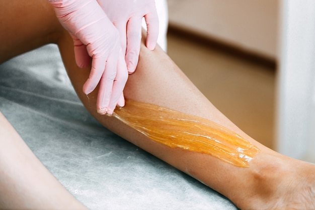 Sugaring sugar waxing feet in the beauty salon.