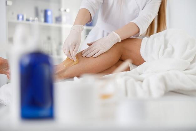 天然素材による砂糖漬け。医者はワックス、蜂蜜を入れます。医学、医療機器、ヘルスケア、美容業界、脱毛の概念。