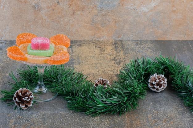 Сладкие мармеладные конфеты с шишками и букетом рождественской елки. фото высокого качества