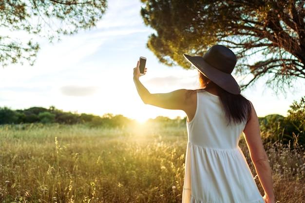 白い自由奔放に生きるスタイルのドレスと大きな黒い帽子の認識できない女性の後ろからの示唆に富むシーン