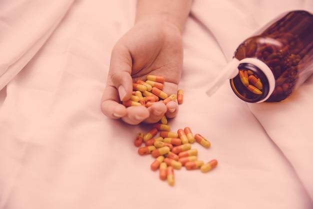 약물 과다 복용 개념에 의한 자살 시도, 많은 캡슐 알약은 약물로 사망하는 여성의 손에 있습니다.