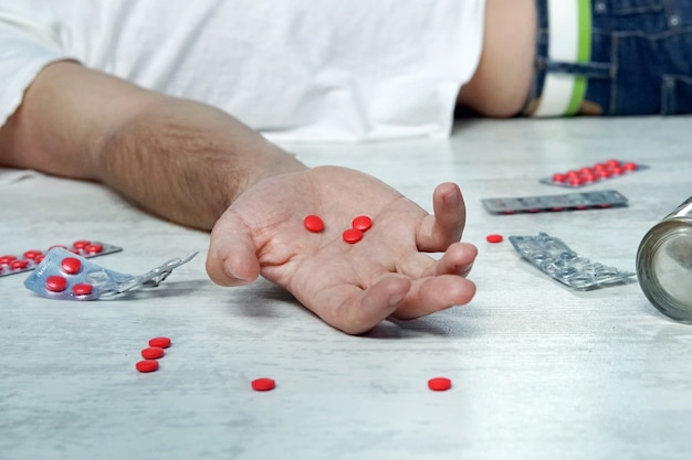 자살, 우울증, 과다복용 개념 밤에 테이블에 알코올과 알약 한 병, 젊은 남자의 손에 빨간 알약을 든 죽은 남자
