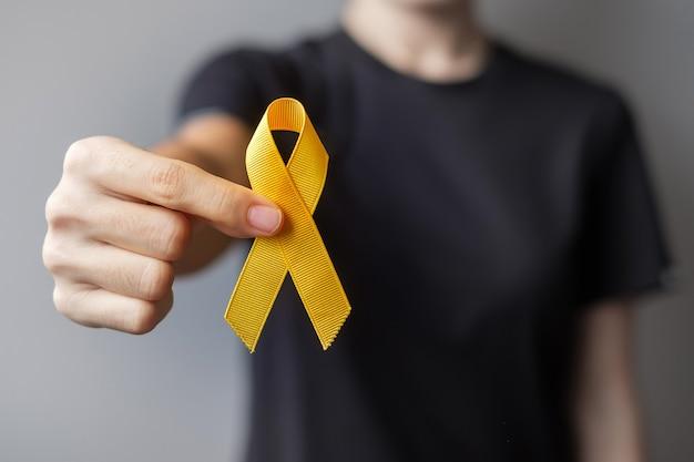自殺予防デー、肉腫、骨肉腫、膀胱がん、小児がん啓発月間、生きている人々や病気をサポートするためのイエローリボン。子供のヘルスケアと世界対がんデーのコンセプト