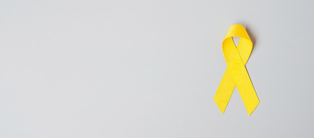 自殺予防、肉腫、骨、膀胱、小児がん啓発月間、生きている人々と病気をサポートするためのイエローリボン。子供のヘルスケアと世界対がんデーのコンセプト