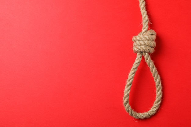 Suicide rope on red wall, space for text
