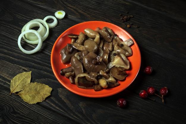 빈티지 테이블에 향신료와 양파와 함께 접시에 절인 Suillus Luteus 또는 Boletus Luteus 버섯. 평면도 프리미엄 사진