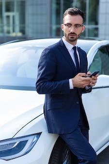 Костюм и галстук. бизнесмен в костюме и галстуке с помощью смартфона, стоя возле автомобиля