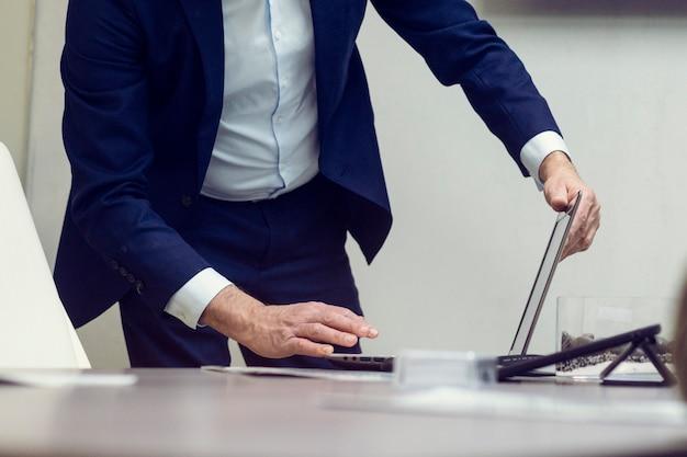 Костюм одетый человек, использующий ноутбук в офисе