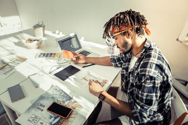 適切な色。彼の新しいプロジェクトに適した色を選択するひげを生やしたプロのインテリアアーティスト