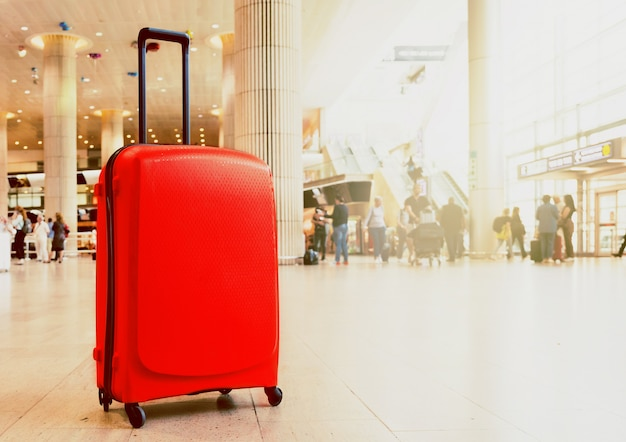 Suitcase in airport airport terminal waiting area with lounge zone as a background. vacation theme concept.