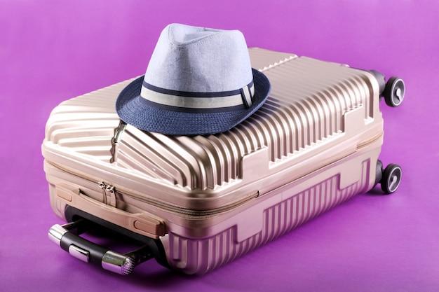 スーツケースと紫色の背景の帽子「旅行」と休日の概念