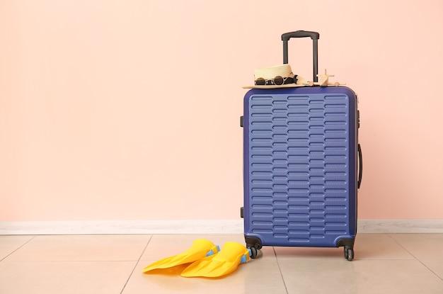 色の壁の近くのスーツケースとビーチ アクセサリー。旅行のコンセプト
