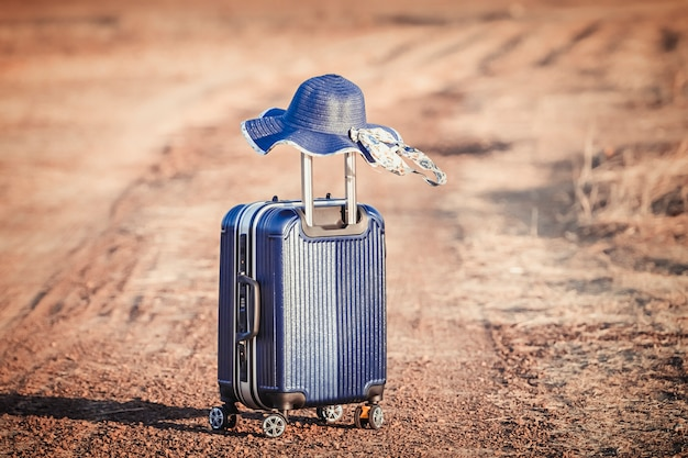 スーツケースと農村フィールドの帽子