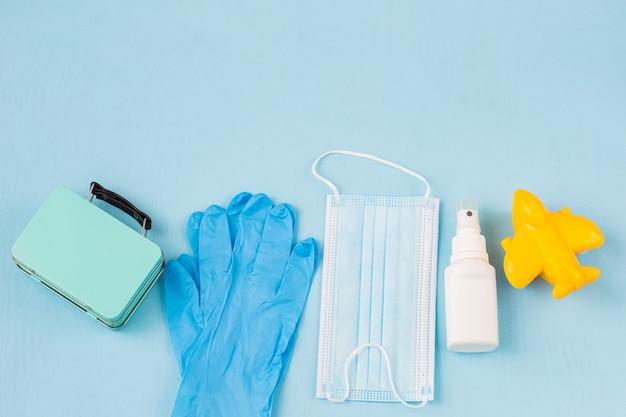 Чемодан, одноразовые перчатки, желтый самолет, стерилизатор для рук и защитная маска