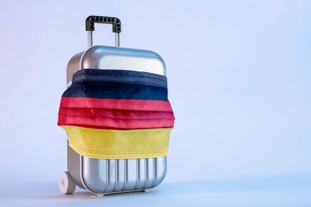 Чемодан для путешествий с медицинской маской и немецким флагом на белом фоне