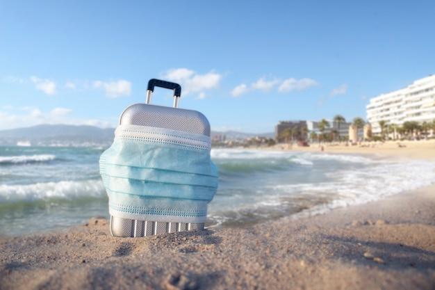 해변에 의료 마스크와 여행 가방