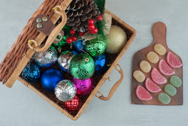 Suitcase full of christmas balls and wooden board with marmalade on white background. high quality photo