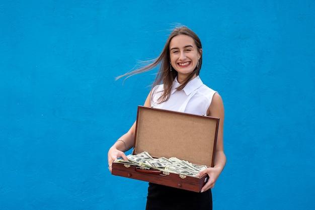 Чемодан с деньгами находится в женских руках, изолированных на синей стене.