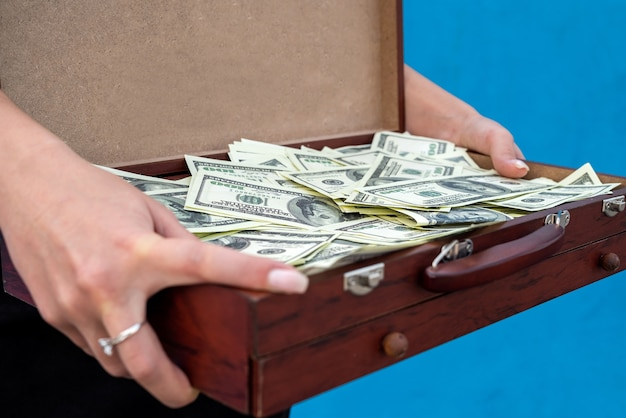 Чемодан с деньгами находится в изолированных женских руках