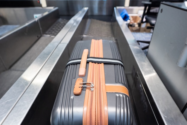 Suitcase on luggage conveyor belt system at check in desk in airport