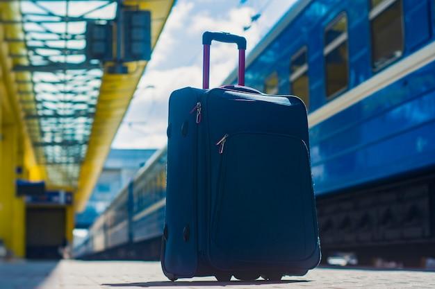 Чемодан на колесах на вокзале на фоне поезда. концепция на тему туризма.